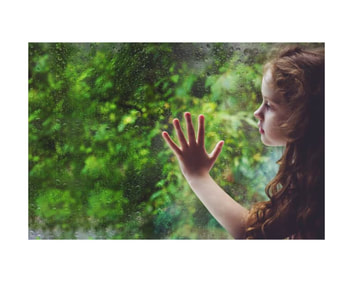 Adorable small girl with long curly red hair holds her hand on clean plate glass window with rain drops on outside and thick green trees beyond.